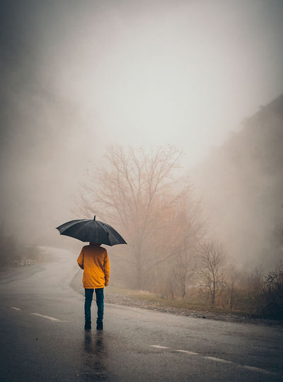 Rear view of boy standing on wet road during rainy season