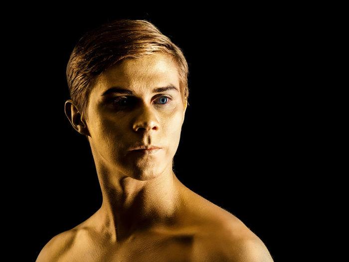 Close-up of male ballet dancer against black background