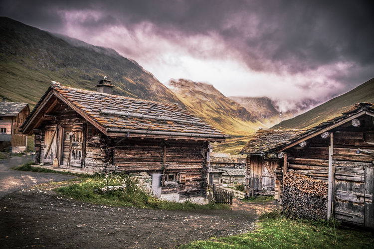 Abandoned house by mountain against sky