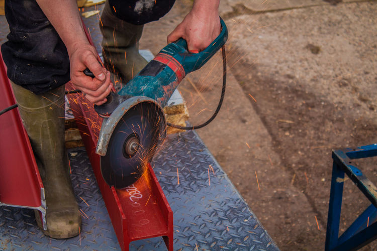 Working grinding machine with firesparks Construction Cutting Industry Machinery Power Wheel Worker Working Carp Cute Fire Sparks Grinder Grinding Machine Hand Human Hand Job Men Metal One Person People Real People Repair Saw Steel Tool