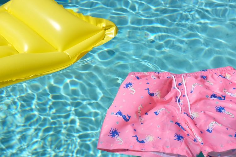 Close-up of raft and shorts floating on swimming pool