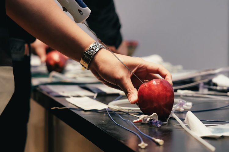 Close-up of man injecting apple on table