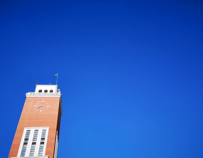 Low angle view of city hall against clear blue sky