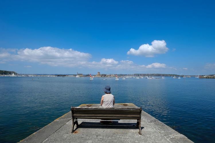 Rear view of woman looking at sea while sitting on bench against blue sky during sunny day