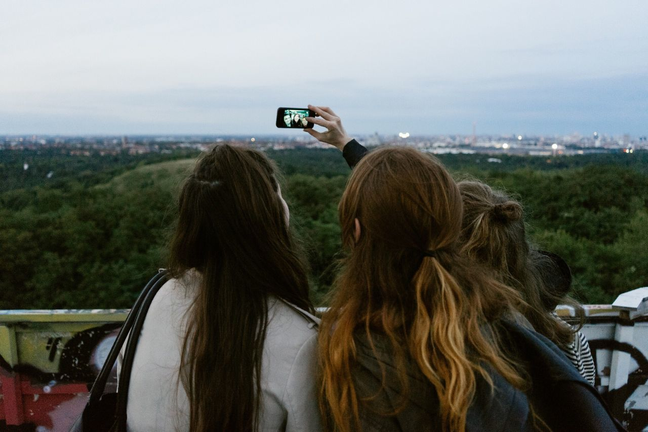 Friends taking a picture of themselves with a mobile phone