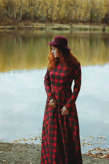 Redhead elegant woman in red dress and hat walking in autumn park.