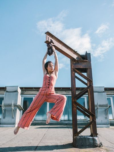 Woman Hanging From Metal Against Blue Sky