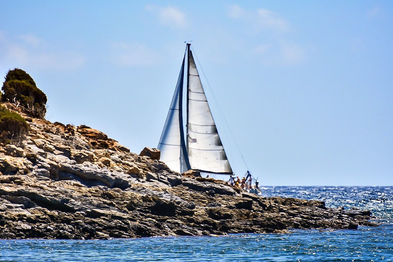 Sailboat By Rock Formation On Sea Against Sky