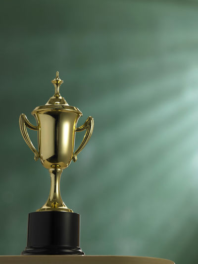 Close-up of trophy on table against green wall