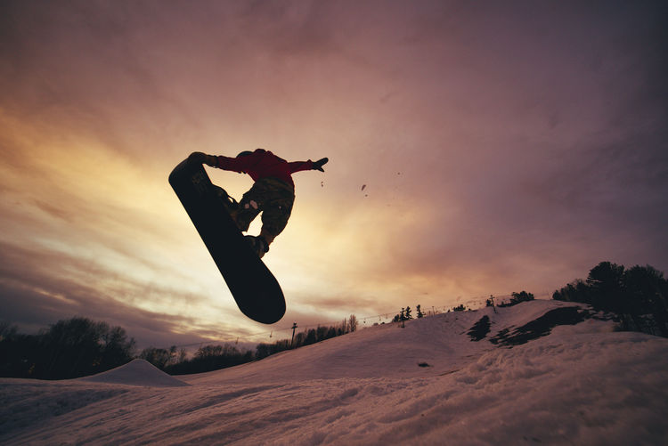 Man on snowboard jumping in snow against sky during sunset