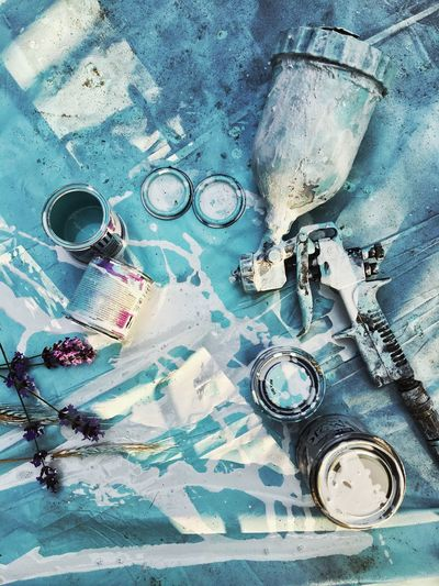 High angle view of work tools with paint cans on table