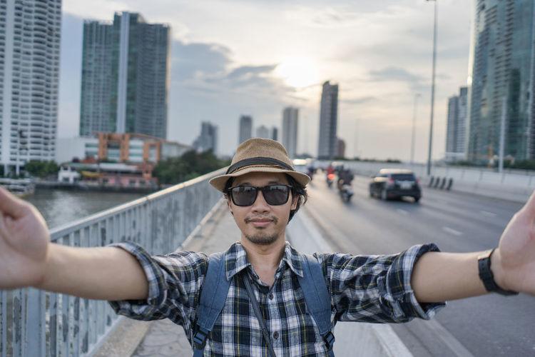 Portrait Of Man Taking Selfie On Bridge During Sunset