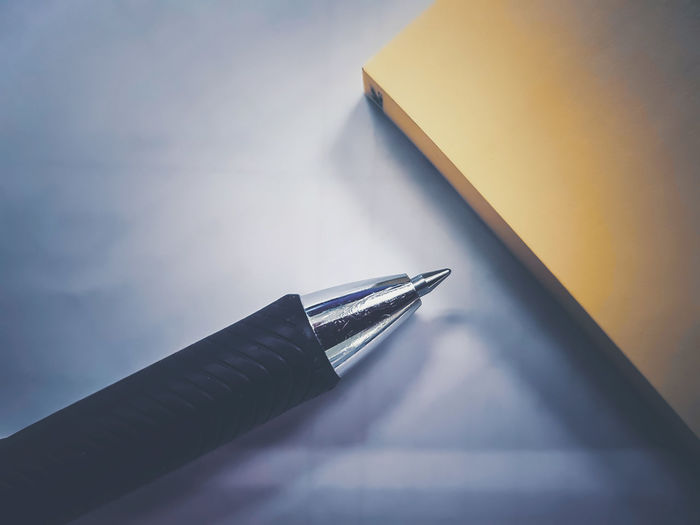 High angle view of pen by book on table