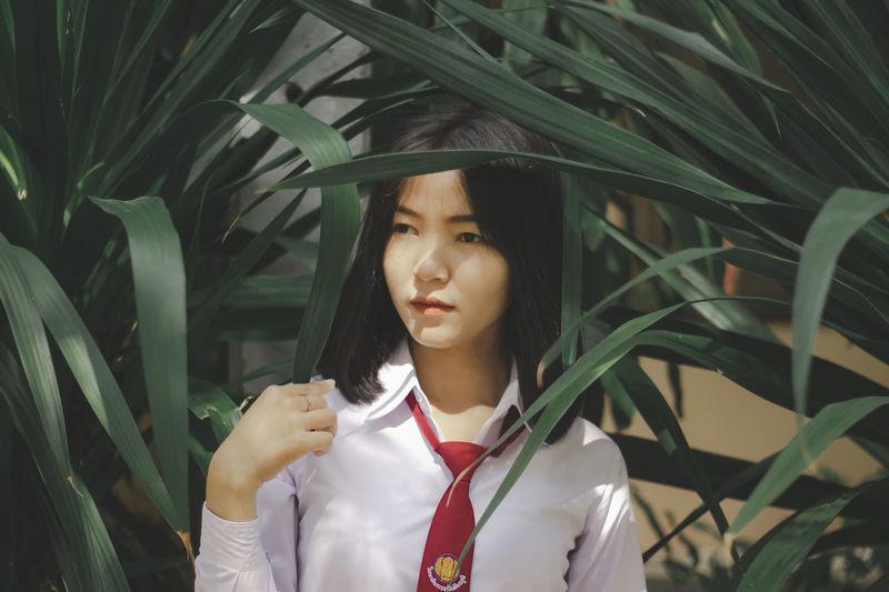Teenage girl looking away amidst plants
