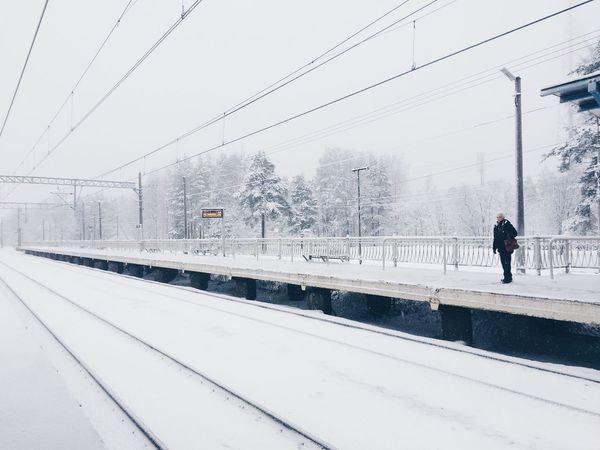 Architecture Building Exterior Built Structure Cable Cold Temperature Day Full Length Leisure Activity Lifestyles Men Nature One Person Outdoors Rail Transportation Railroad Station Platform Real People Sky Snow Snowing Transportation Tree Walking Weather Winter Young Adult