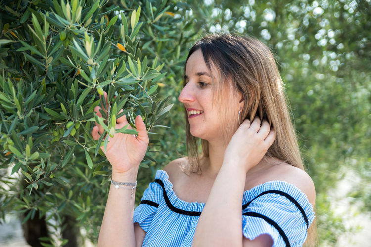 Portrait of smiling woman holding strawberry outdoors