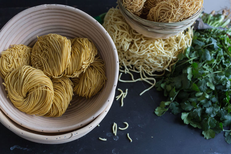 High angle view of dry noodles with parsley on table