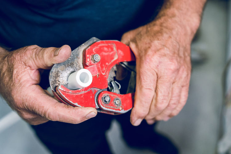 Midsection of man holding work tool