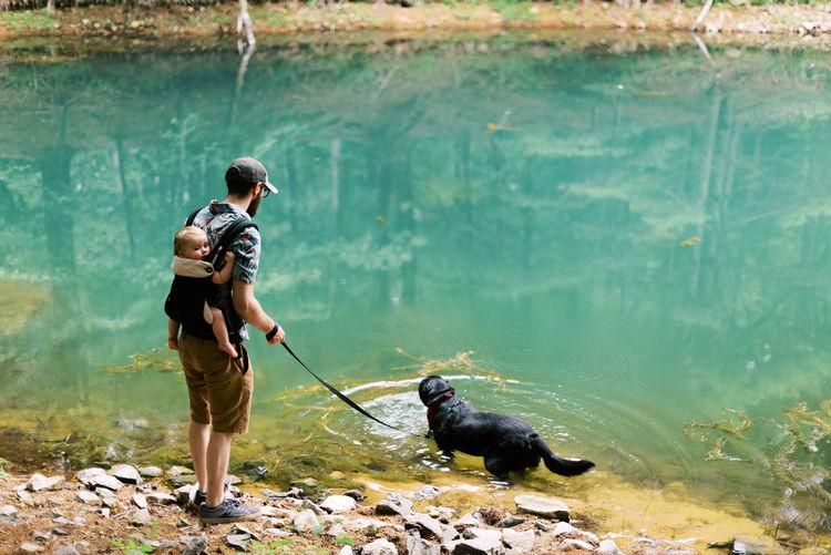 Full length of man holding dog standing at shore