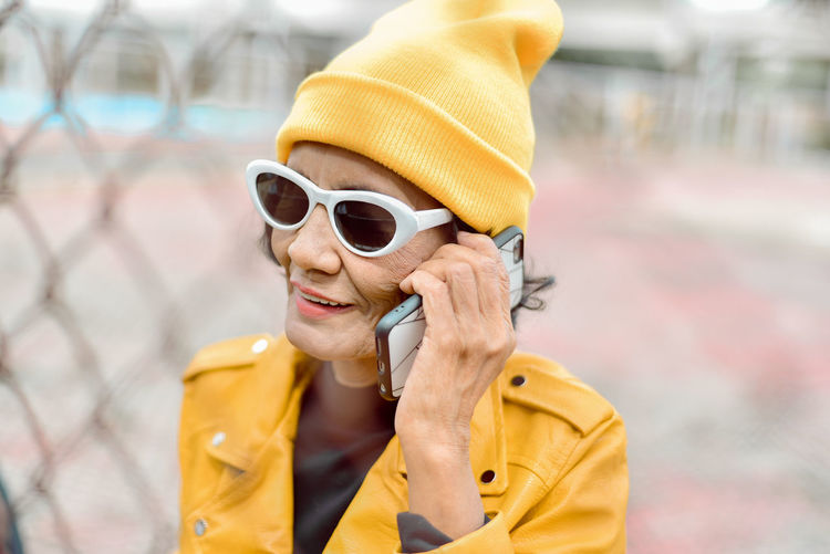 Senior woman talking on phone while standing by chainlnk fence