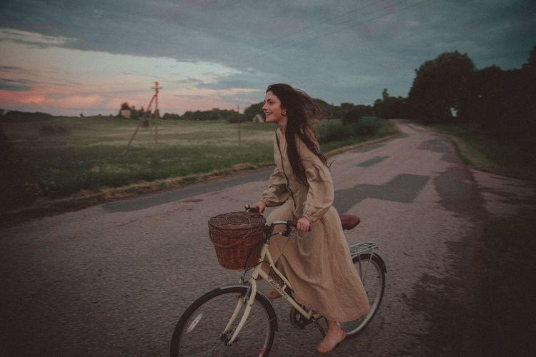 Woman riding bicycle on road against sky