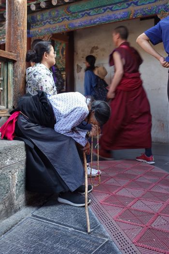 Adult Architecture Belief Chinese Culture Ethnic Group Of People Lifestyles National Dress People Place Of Worship Real People Religion Sitting Spirituality Temple Temple - Building Tibet Traditional Clothing Women