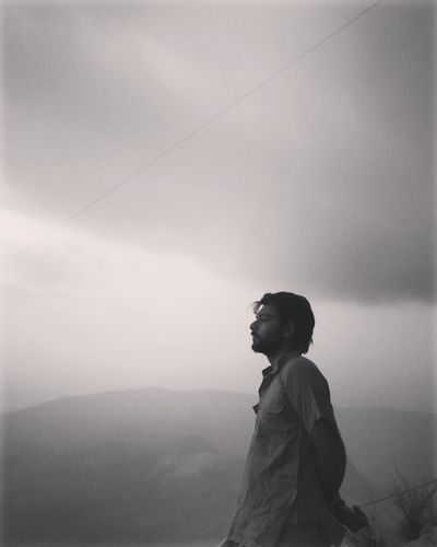 Side view of man looking at mountain against sky