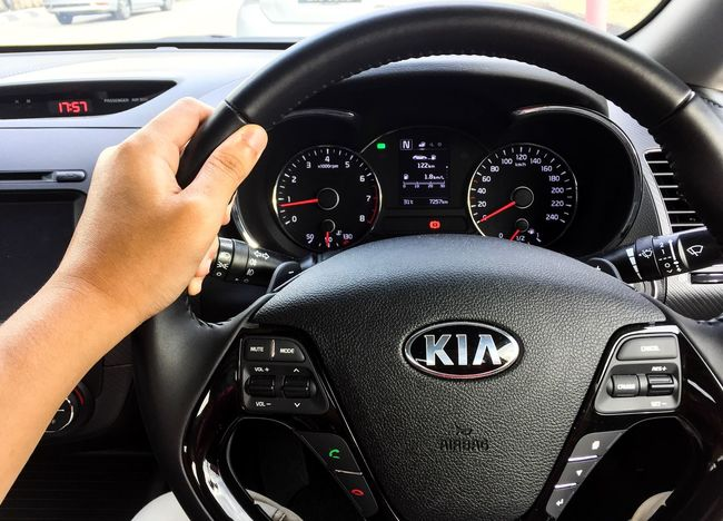 Hand holding car steering of KIA automobile. Kia Motor Corporation, head quartered in Seoul, is south Korea's second-largest automobile manufacturer. Transportation Automobile Holding Steering Driving In My Car Driving Car Speedometer Land Vehicle Control Mode Of Transport Human Body Part Cockpit Speed Gauge Human Hand Piloting Day Control Panel Close-up