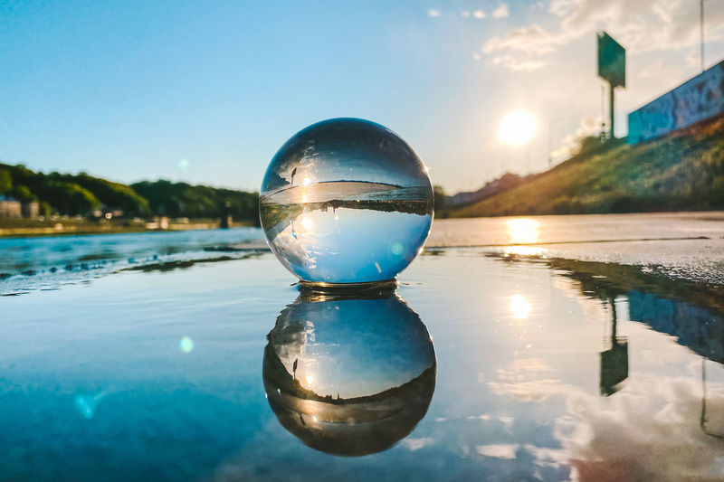 Close-up of crystal ball on puddle on road against blue sky