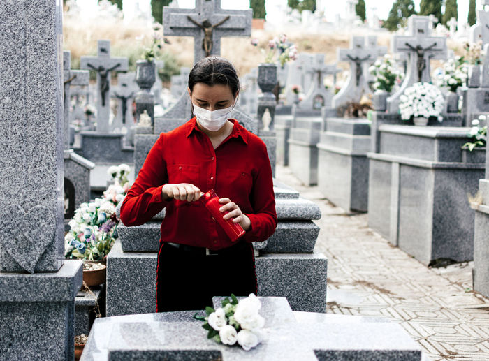 Young woman wearing mask standing at cemetery