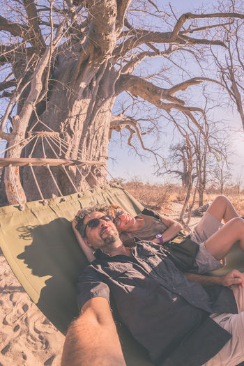 Couple taking selfie on hammock hanging from huge Baobab tree in the african savannah. Fisheye view, toned image. Wilderness safari and adventure in Africa. Bare Tree Bonding Branch Day Father Happiness Human Hand Leisure Activity Lifestyles Love Mature Men Men Nature Outdoors People Real People Sitting Sky Togetherness Tree Two People Young Adult