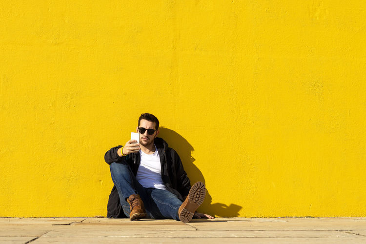 Young man sitting on yellow wall