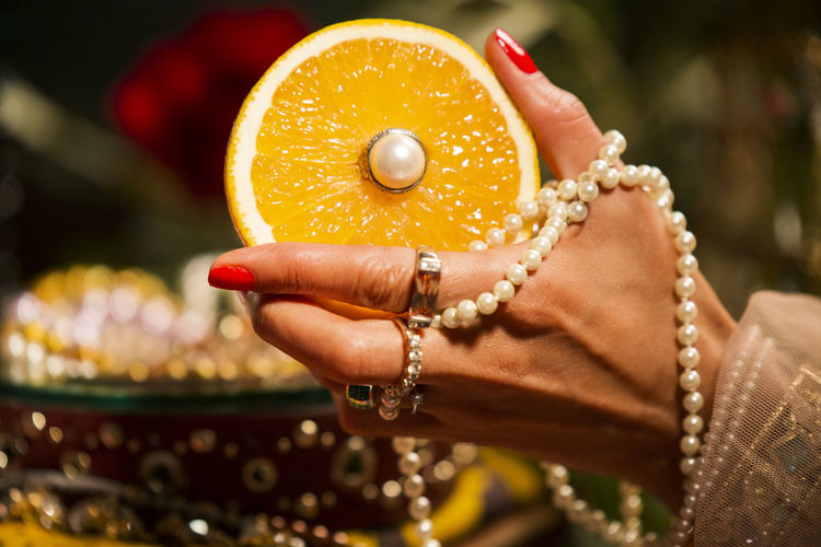 a woman enjoying fruits and jewels Abundance Celebration Wealth Jewelry Pearls Decoration Orange One Person Focus On Foreground Close-up Human Hand Hand Women Human Body Part Holding Adult Real People Bracelet Pearl Jewelry Ring Necklace Lifestyles Day Nail