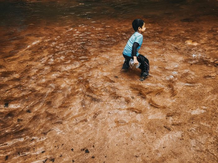 Boy in a river full of fish River Childhood Child Boys Full Length Males  One Person Real People Nature Playing Men Casual Clothing High Angle View Leisure Activity Offspring Lifestyles Land Outdoors Sand Day Innocence