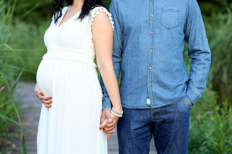 Man Holding Hands Of Pregnant Woman While Standing At Park