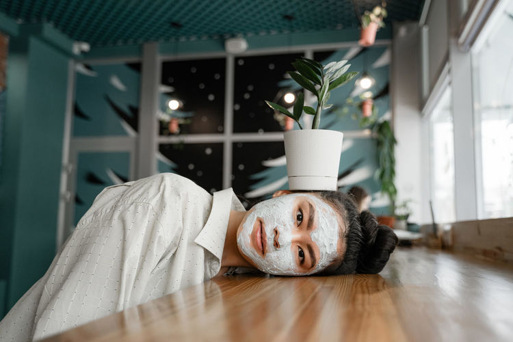 Portrait of woman with face mask lying on table at home