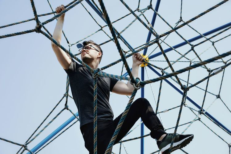 Low Angle View Of Mid Adult Man Climbing Rope Against Clear Sky