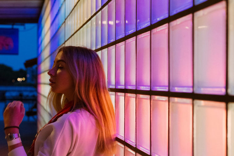 Illumination Adult Beautiful Woman Casual Clothing Contemplation Focus On Foreground Hairstyle Headshot Human Face Illuminated Indoors  Leisure Activity Lifestyles Looking Looking Away Neon Nightlife One Person Portrait Profile View Purple Real People Side View Women Young Adult Young Women