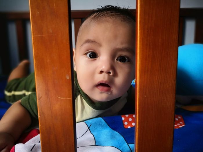 Portrait of cute baby boy lying on crib at home