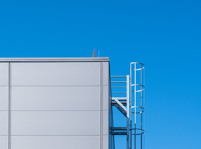 Low angle view of building with fire escape against clear blue sky