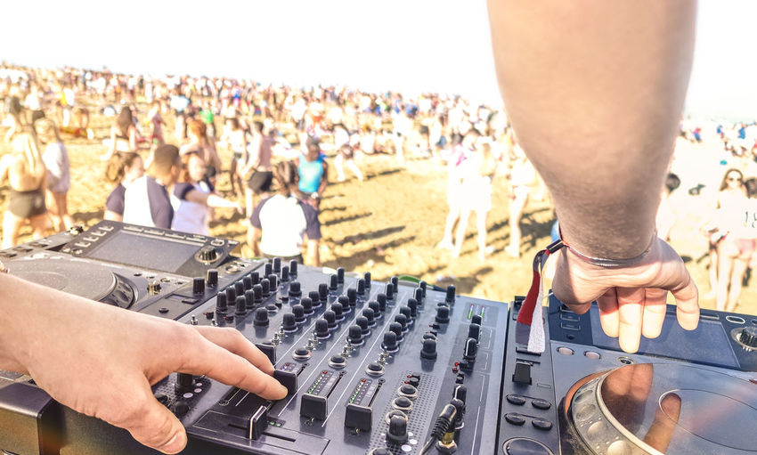 Cropped Image Of Dj Using Sound Mixer With Crowd In Background During Event