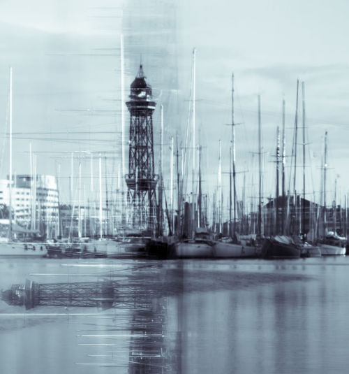Sailboats in sea against buildings in city