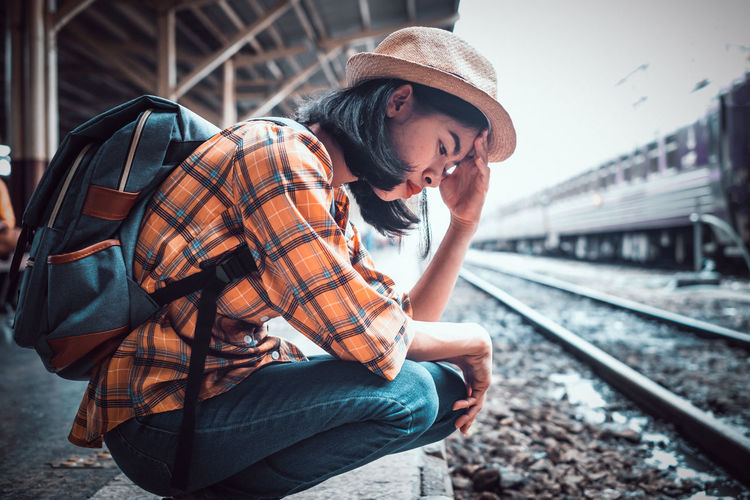 Young man looking down at railroad station