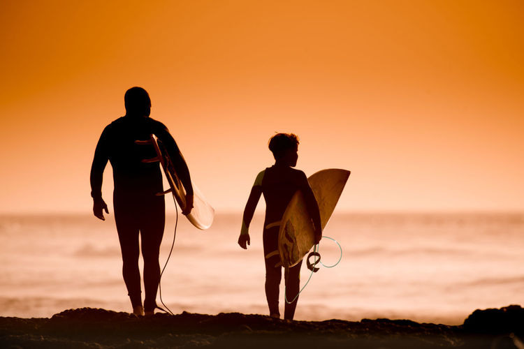 Silhouette father and son with surfboard at beach against sky during sunset