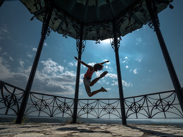 Low angle view of woman jumping in gazebo against sky