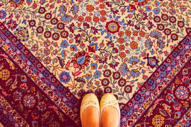 Low section of woman wearing shoes while standing on carpet