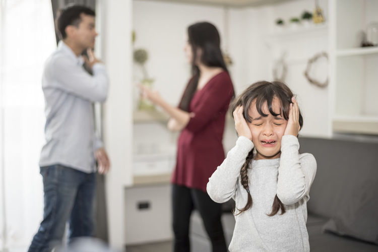 Crying daughter against parents fighting in house