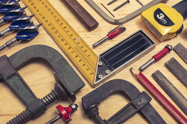 High angle view of various work tools on wooden table