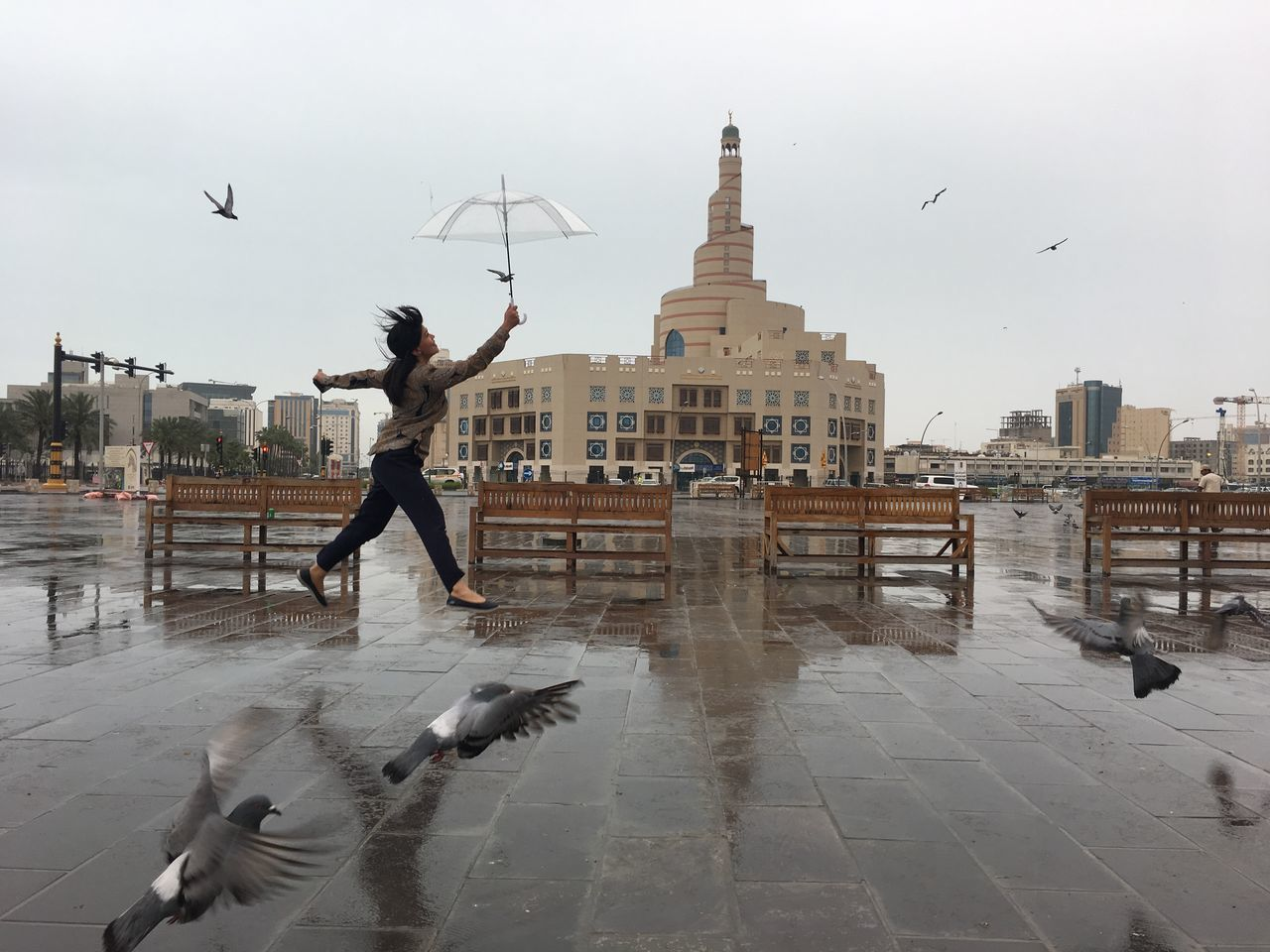 mid-air, bird, real people, flying, motion, building exterior, architecture, built structure, spread wings, animals in the wild, men, leisure activity, animal wildlife, large group of animals, lifestyles, flock of birds, outdoors, full length, one person, day, water, city, jumping, seagull, energetic, sky, nature, mammal