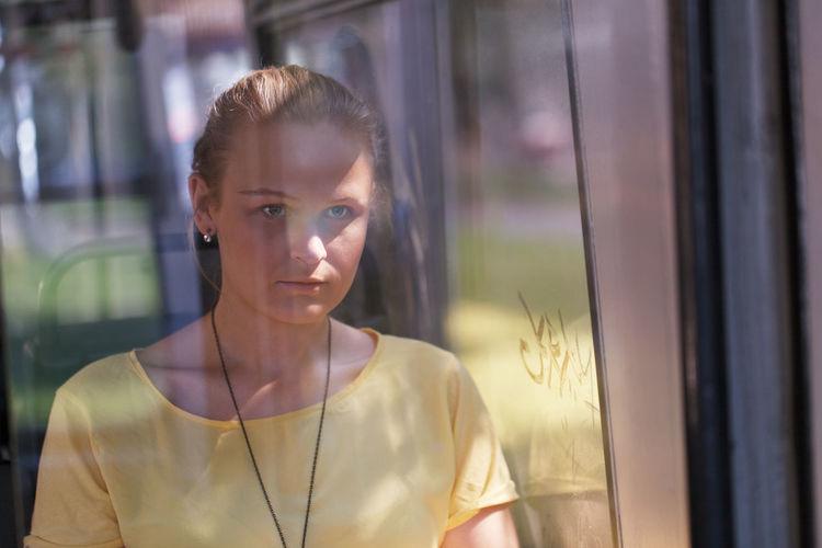 Woman seen from bus window